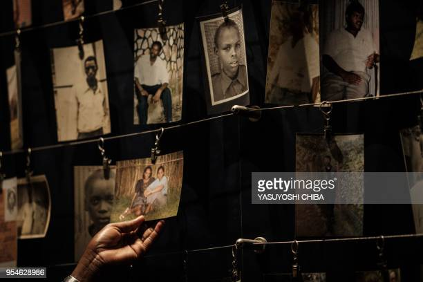 A picture taken on April 29 2018 shows a visitor looking at victims' portraits at the Kigali Genocide Memorial in Kigali Rwanda According to the main...