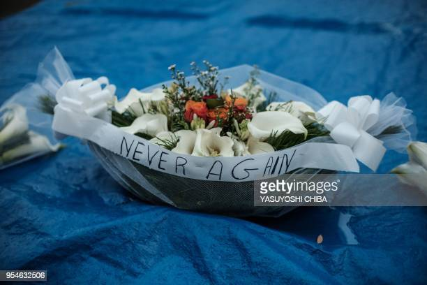 A picture taken on April 29 2018 shows flower offerings on a mass grave at the Kigali Genocide Memorial in Kigali Rwanda According to the main...