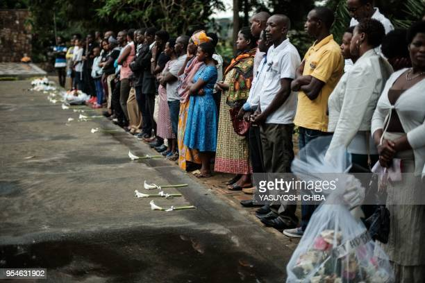 A picture taken on April 29 2018 shows people praying in front of the mass grave at the Kigali Genocide Memorial in Kigali Rwanda According to the...
