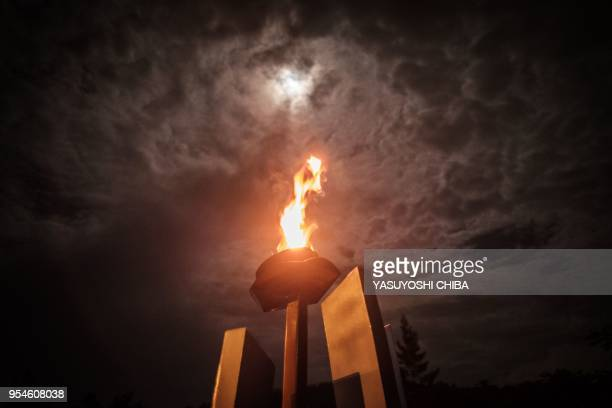 A picture taken on April 29 2018 shows the flame of Remembrance under a full moon at the Kigali Genocide Memorial in Kigali Rwanda According to the...