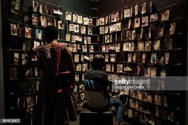 A picture taken on April 29 2018 shows visitors looking at victims' portraits at the Kigali Genocide Memorial in Kigali Rwanda According to the main...