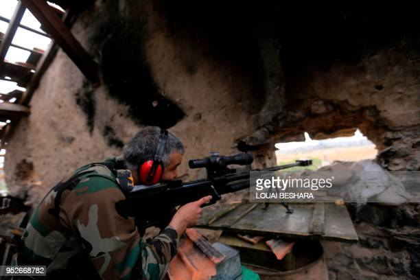 TOPSHOT A picture taken on April 29 during a government guided tour in Damascus' southern alQadam neighbourhood shows Syrian army sniper taking aim...