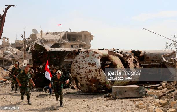 TOPSHOT A picture taken on April 29 during a government guided tour in Damascus' southern alQadam neighbourhood shows Syrian army forces running for...
