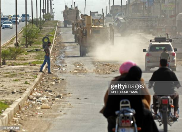 TOPSHOT A picture taken on April 3 2018 shows vehicles of USbacked coalition forces driving in the northern Syrian town of Manbij On the outskirts of...