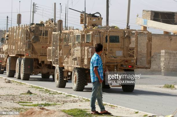A picture taken on April 3 2018 shows vehicles of USbacked coalition forces driving in the northern Syrian town of Manbij On the outskirts of Syria's...