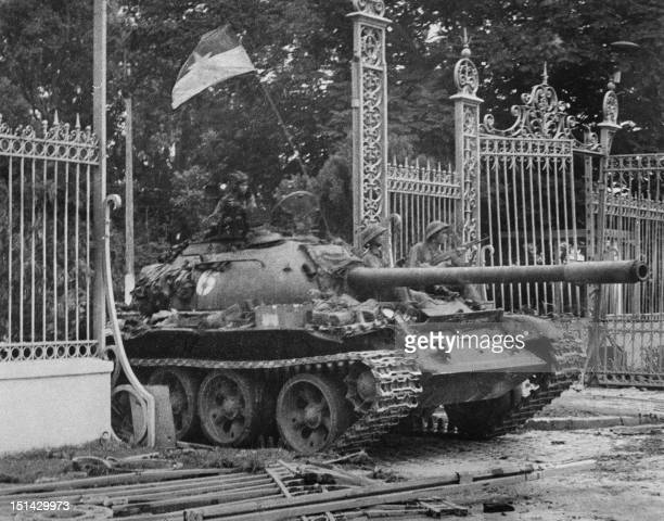 A picture taken on April 30 1975 in Saigon shows a tank of the North Vietnamese Army smashing in the gate of the South Vietnamese presidential palace...