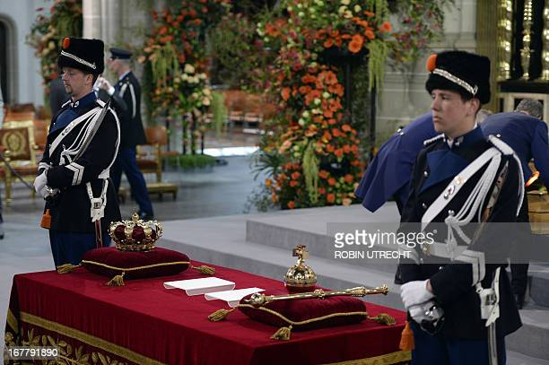 A picture taken on April 30 2013 in the Nieuwe Kerk in Amsterdam The Netherlands shows guards standing next to the Royal Crown and Scepter at the...