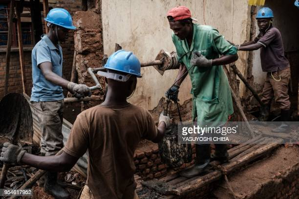 A picture taken on April 30 2018 shows workers taking out soil from a pit which was used as mass grave during 1994 Rwandan genocide and hid under a...