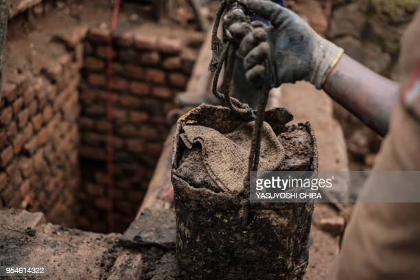 A picture taken on April 30 shows a worker collecting a victim's knitted hat taken out from a pit which was used as mass grave during 1994 Rwandan...