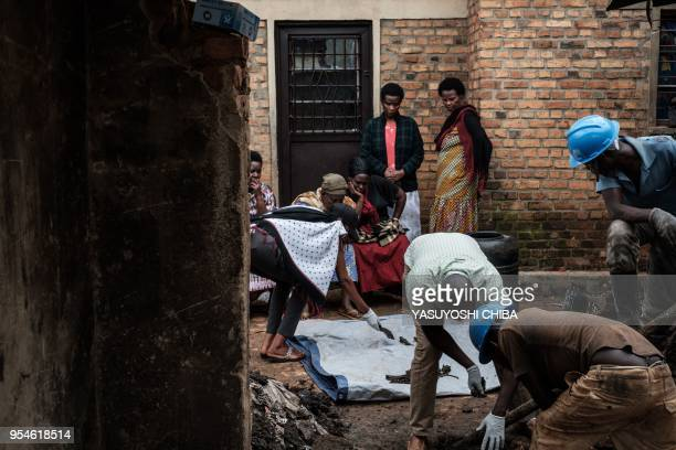 A picture taken on April 30 shows people collect victims' bones from a pit which was used as mass grave during 1994 Rwandan genocide and hidden under...