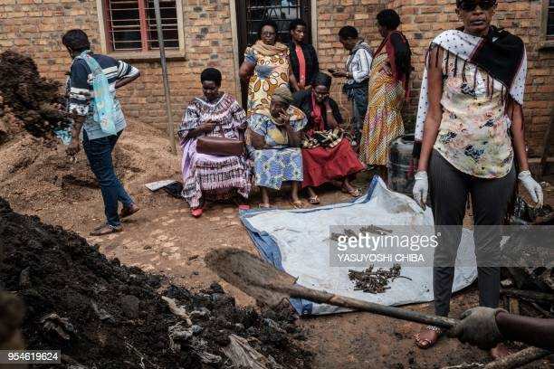 TOPSHOT A picture taken on April 30 shows people collect victims' bones from a pit which was used as mass grave during 1994 Rwandan genocide and...