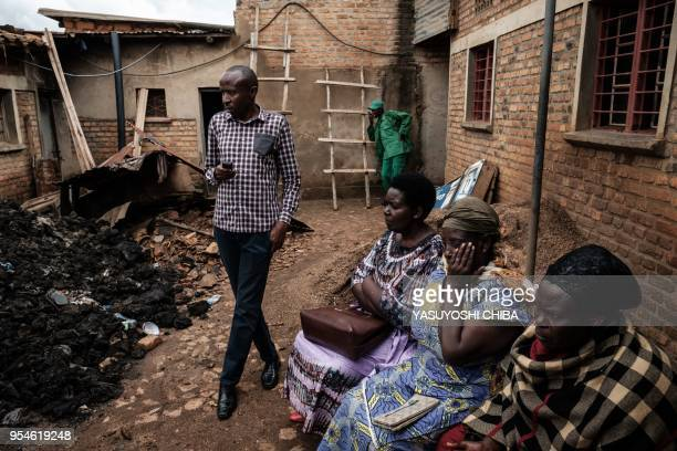 A picture taken on April 30 shows people wait to see items of victims taken out from a pit which was used as mass grave during 1994 Rwandan genocide...