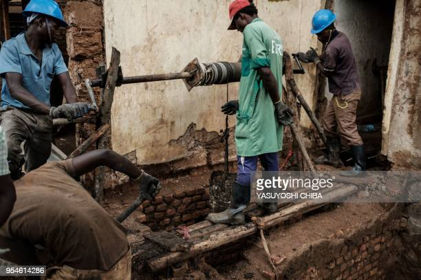 A picture taken on April 30 shows workers looking for victims' bones from a pit which was used as mass grave during 1994 Rwandan genocide and hidden...