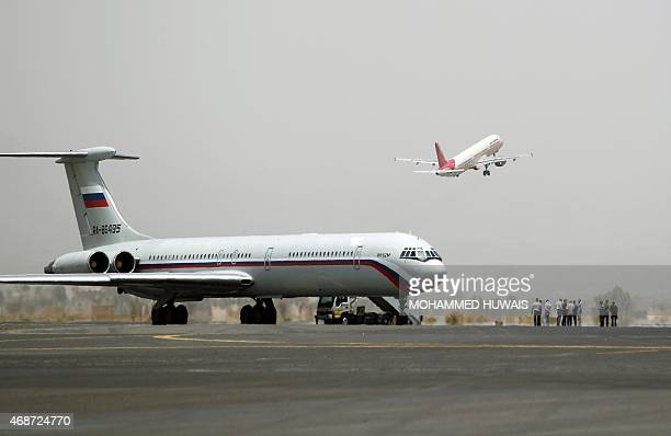 A picture taken on April 6 2015 shows an aircraft of Air India taking off behind an aircraft of the Russian Federation Air Force stationned on the...