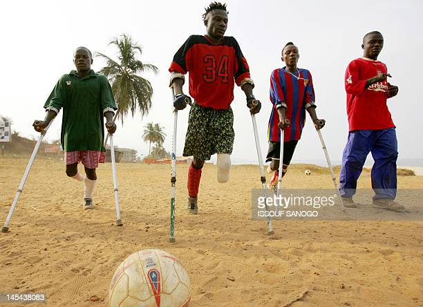 A picture taken on April 7 2006 shows players of the Sierra Leone civil war amputees football team on a beach in Freetown Former Liberian president...