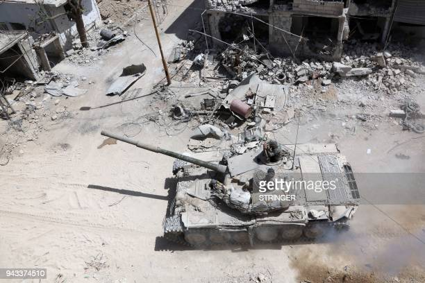 TOPSHOT A picture taken on April 8 shows Syrian Army soldiers advancing in an area on the eastern outskirts of Douma as they continue their fierce...