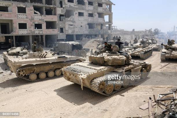 TOPSHOT A picture taken on April 8 shows Syrian Army soldiers gathering in an area on the eastern outskirts of Douma as they continue their fierce...