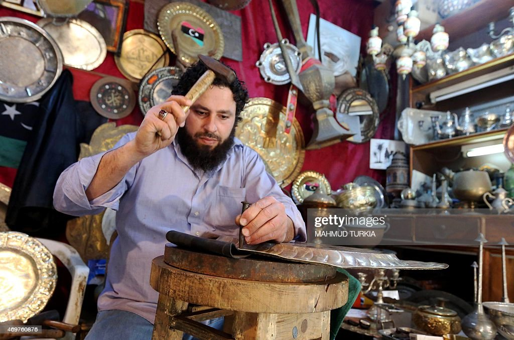 A picture taken on April 9, 2015 shows a Libyan craftsman sculpting brass inside a workshop in the Old City of Tripoli, Libya's capital. For over two thousand years the old city has been the heartbeat of the Libyan capital, with its whitewashed historic buildings and vibrant markets but ongoing clashes and the rise of jihadist groups have put a dent in the old town's economy and prospect.