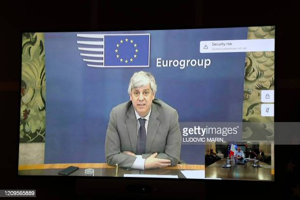A picture taken on april 9 2020 shows Eurogroup chairman Mario Centeno displayed on a TV screen during an Eurogroup videoconference with French...