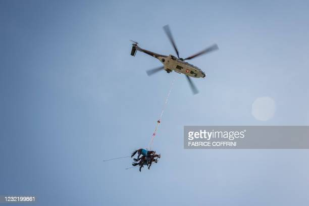 Picture taken on April 9, 2021 in Saignelegier shows three horses being airlifted together during a test by Swiss army forces on hoisting horses with...
