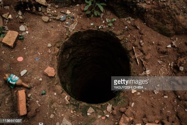 A picture taken on April 9 shows a pit which was used as mass grave during 1994 Rwandan genocide and hidden under a house is seen in Kabuga in the...