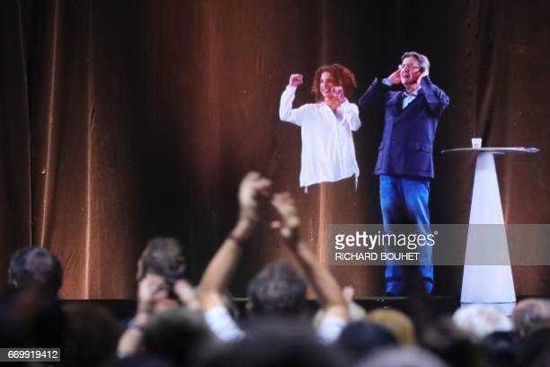 A picture taken on April on April 18 in Le Port in the French overseas island of La Reunion shows a hologram of French presidential election...