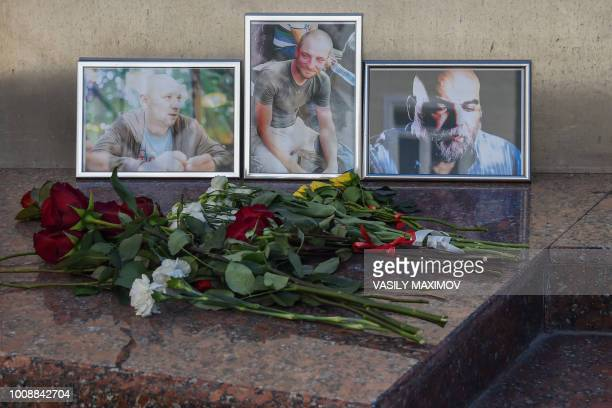 A picture taken on August 1 2018 shows flowers left in front of the photographs of Russian journalists Alexander Rastorguyev Kirill Radchenko and...