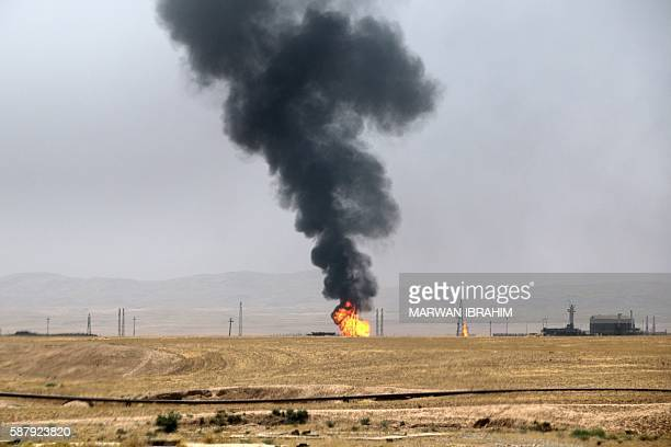 A picture taken on August 10 2016 shows flames and smoke rising from a well on fire at Bai Hassan oil field the largest in Iraqi oilrich Kirkuk...