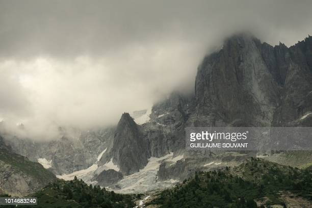 A picture taken on August 10 2018 shows a detail of Petite Aiguille Verte hidden by clouds part of the group of peaks Aiguilles de Chamonix in the...