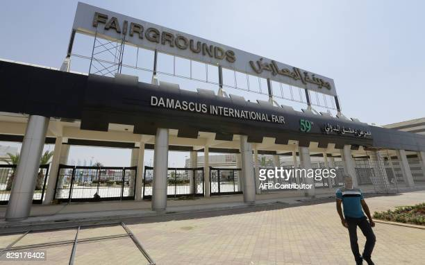 A picture taken on August 10 shows people walking past the Damascus International Fair in the Syrian capital countryside The fair is scheduled to...