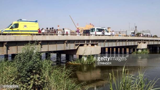 A picture taken on August 11 2018 shows an ambulance and Egyptian police forces and investigators gathered on a bridge along the Nile where a suicide...