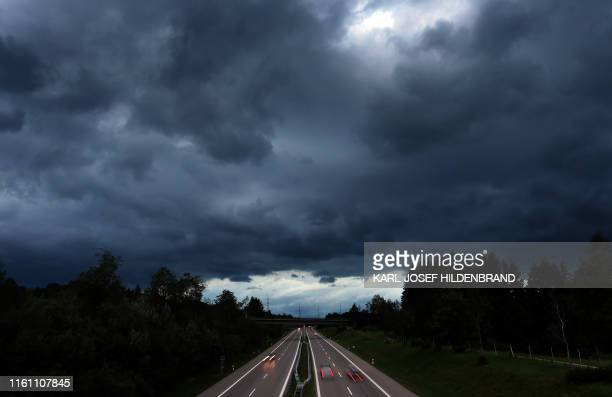 Picture taken on August 11, 2019 shows black clouds above cars driving on the A7 motorway near Oy-Mittelberg, southern Germany. / Germany OUT