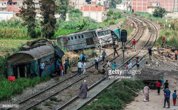A picture taken on August 12 2017 shows a general view of people observing the wreckage of a fatal train collision in the area of Khorshid on the...