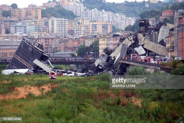 TOPSHOT A picture taken on August 14 2018 in Genoa shows a section of the Morandi motorway bridge that collapsed earlier injuring several people...