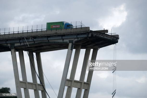 TOPSHOT A picture taken on August 14 2018 in Genoa shows a view of the Ponte Morandi motorway bridge after one of its section collapsed injuring...