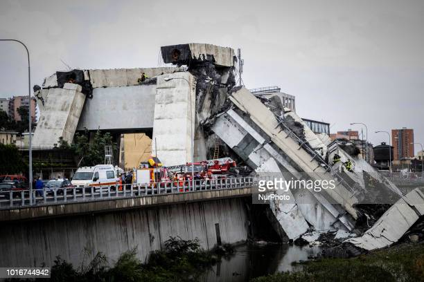 Picture taken on August 14, 2018 shows rescue workers on a part of a Morandi motorway bridge after a section collapsed earlier in Genoa. - At least...