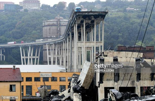 A picture taken on August 14 2018 shows vehicles standing on a part of a giant motorway bridge after a section collapsed earlier in Genoa At least 22...