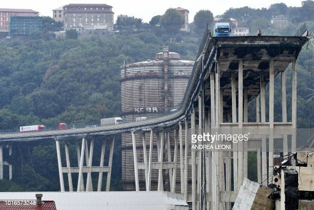 TOPSHOT A picture taken on August 14 2018 shows vehicles standing on a part of a Morandi motorway bridge after a section collapsed earlier in Genoa...