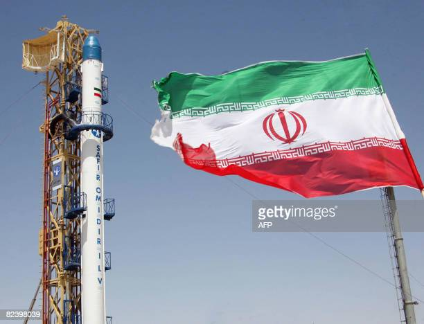 A picture taken on August 16 2008 shows an Iranian flag fluttering in front of Iran's Safir Omid rocket which is capable of carrying a satellite into...