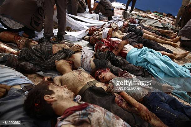 A picture taken on August 16 2015 shows dead bodies linedup on the ground following air strikes by Syrian government forces on a marketplace in the...