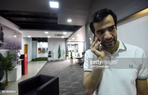 A picture taken on August 17 2017 shows Saudi programmer Zainalabdin Tawfiq developer of the Sarahah app talking on his cell phone at his office in...