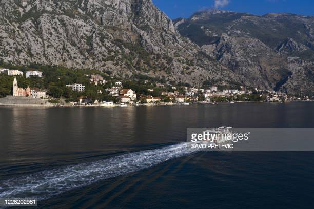 Picture taken on August 17, 2020 shows a boat cruising across Montenegro's mountain-ringed Kotor bay. - The pandemic-triggered peace is tinged with...