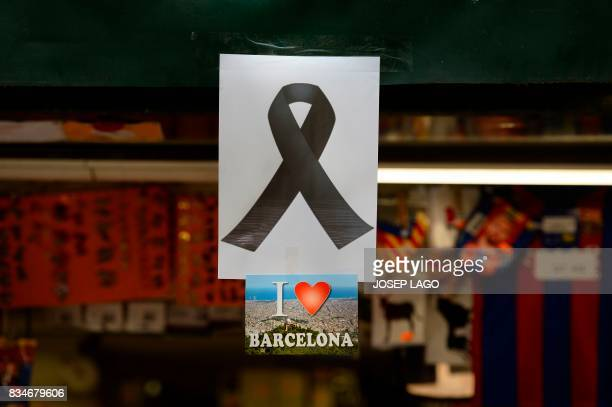 A picture taken on August 18 2017 shows a black ribbon stuck above a postcard of Barcelona reading 'I love Barcelona' both displayed on the window of...