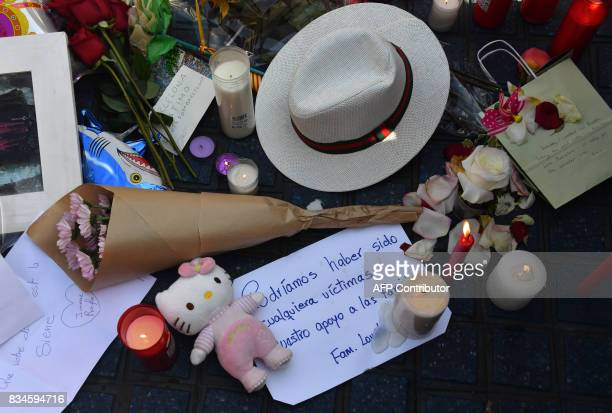 A picture taken on August 18 2017 shows a hat flowers candles and other items set up on the Las Ramblas boulevard in Barcelona to pay tribute to the...