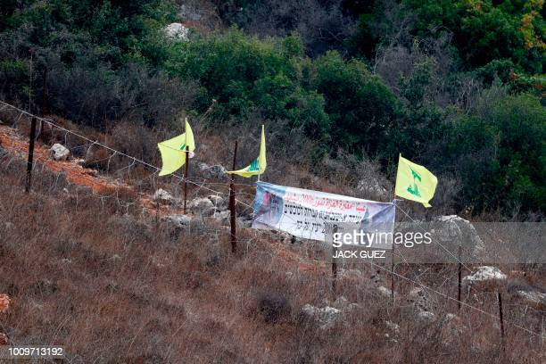 A picture taken on August 2 2018 shows Hezbollah's flags flying at Point 105 on the IsraelLebanon border where eight Israeli soldiers were killed on...