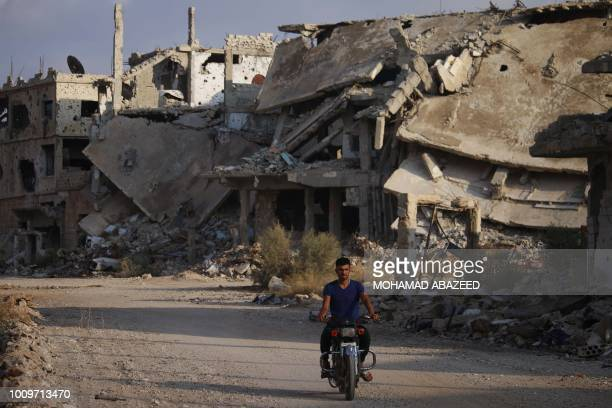 A picture taken on August 2 shows a man riding a motorcycle past destroyed buildings in the oppositionheld southern city of Daraa