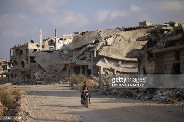 Picture taken on August 2 shows a man riding a motorcycle past destroyed buildings in the opposition-held southern city of Daraa.
