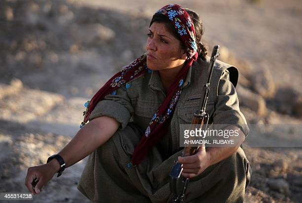 A picture taken on August 21 2014 shows a woman Kurdistan Workers Party fighter guarding a post on the front line in the Makhmur area near Mosul...