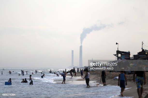 A picture taken on August 21 2015 in the northern Gaza Strip shows Palestinians on the beach as smoke billows from the chimneys of a power station in...