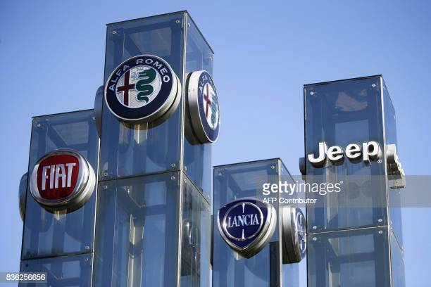 A picture taken on August 21 2017 at a car dealer in Turin shows the logos of Jeep Fiat Lancia and Alfa Romeo automobile company brands of Fiat...